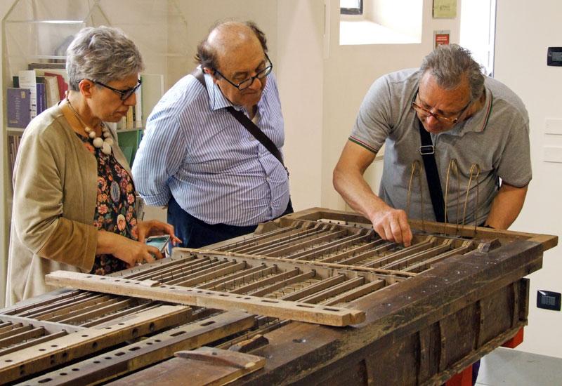 Il direttore del museo di organaria di Crema Sig. Sebastiano Guerini spiega con entusiasmo il funzionamento di un antico somiere a vento; il prof. Marchetti e la Sig.ra Spezzaferri seguono interessati.