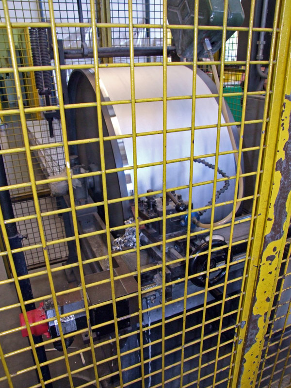 """Il tornio """"a botte"""" con la lastra montata pronta per la prima passata di sgrossatura. Questo tipo di tornio è molto particolare e anche molto raro da rintracciare nelle officine; viene utilizzato per portare allo spessore voluto la lastra in lega di Fig.7. Sulla sinistra del grande cilindro si può osservare la parte iniziale appena lavorata (è la parte lucente)."""