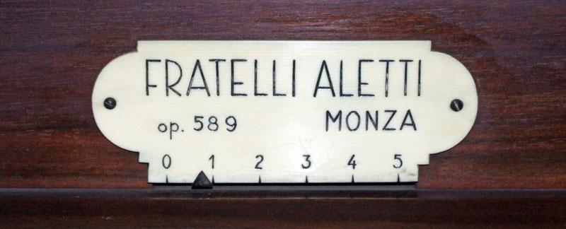 """Targhetta avvitata sulla consolle, riportante la scritta """"Fratelli Aletti, Monza, op. 589""""."""