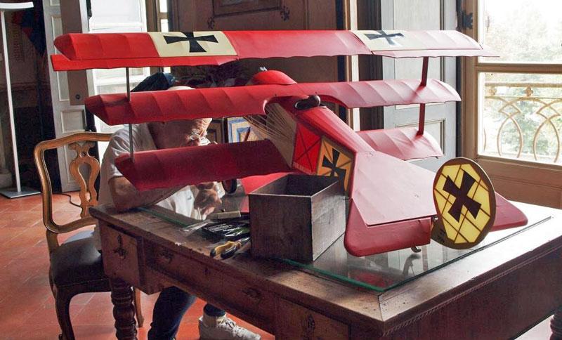 """Figura 7 - Olimpio, fratello di Andrea Ferrero è un bravissimo modellista aeronautico; in questa fotografia lo vediamo alle prese con un piccolo lavoro di sistemazione del notissimo triplano Fokker Dr.1 di Manfred von Richthofen : il mitico """"Barone Rosso"""". L'aereo è ovviamente stato interamente costruito da Olimpio."""
