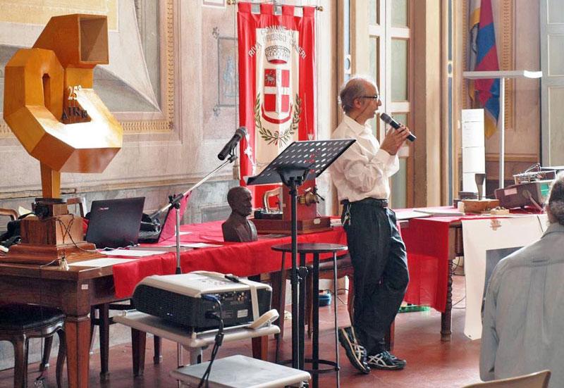 Figura 8 - Il Prof. Luca Torchio accanto ai suoi apparecchi di sperimentazione spiega al pubblico presente alcune proprietà delle radio onde.