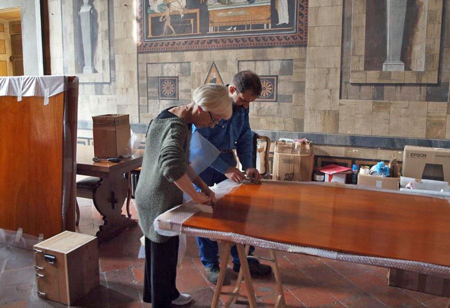 """Figura 9 - Le prime operazioni di montaggio per l'allestimento della mostra; Antonella Corno e il sottoscritto liberano i tabelloni di legno dagli imballi. I tabelloni ospiteranno circa il 25% della documentazione storico-cartacea della prestigiosa fabbrica di organi a canne """"Fratelli Aletti"""" di Monza."""