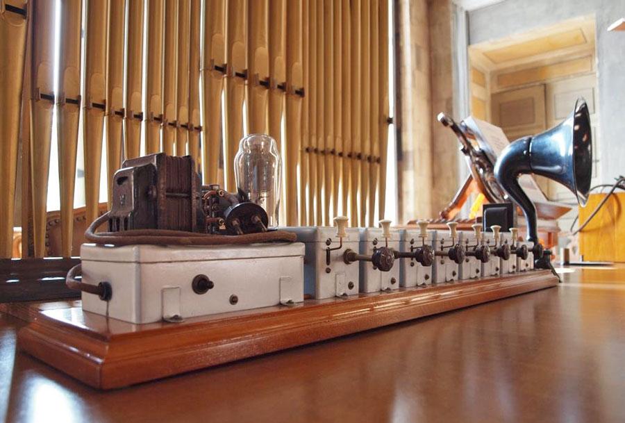 """Figura 11 - Il pezzo storico più importante della mostra di organaria: il primo organo elettronico italiano funzionante con lampade a gas inerte. Fu brevettato con attestato di privativa industriale, rilasciato dal """"Ministero delle Corporazioni"""", il 19/9/1939. Il numero di serie del brevetto è 378.223. Anche la facciata di canne d'organo che si vede sullo sfondo è originale della ditta Aletti; le canne sono state costruite daPietro Alzati, il cannifonista della ditta."""