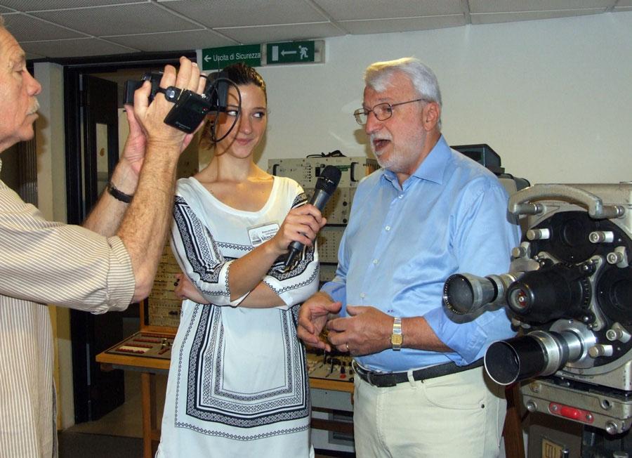 Figura 18 - Casi durante l'intervista che una TV locale ha effettuato in un angolo del museo dedicato alla televisione; la figlia Valentina gli sorregge il microfono.
