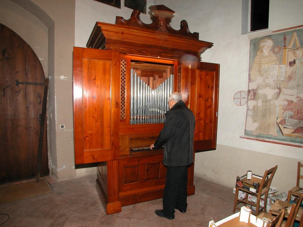Don Mario Conconi osserva il suo organo perfettamente restaurato nei più piccoli particolari.