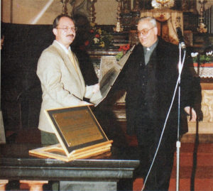 Il dr. Biagio Longo (AEM) riceve una stampa del rinnovato organo da Don Pietro Agnelli, parroco di Grosio