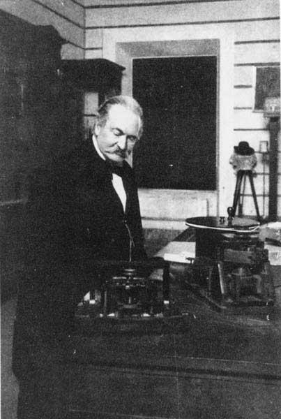 Lo scienziato italiano Antonio Pacinotti (1841-1912) nel suo laboratorio; in primo piano è chiaramente visibile la dinamo da lui ideata; come si può osservare è identica a quella della stampa raffigurata in Fig.10.