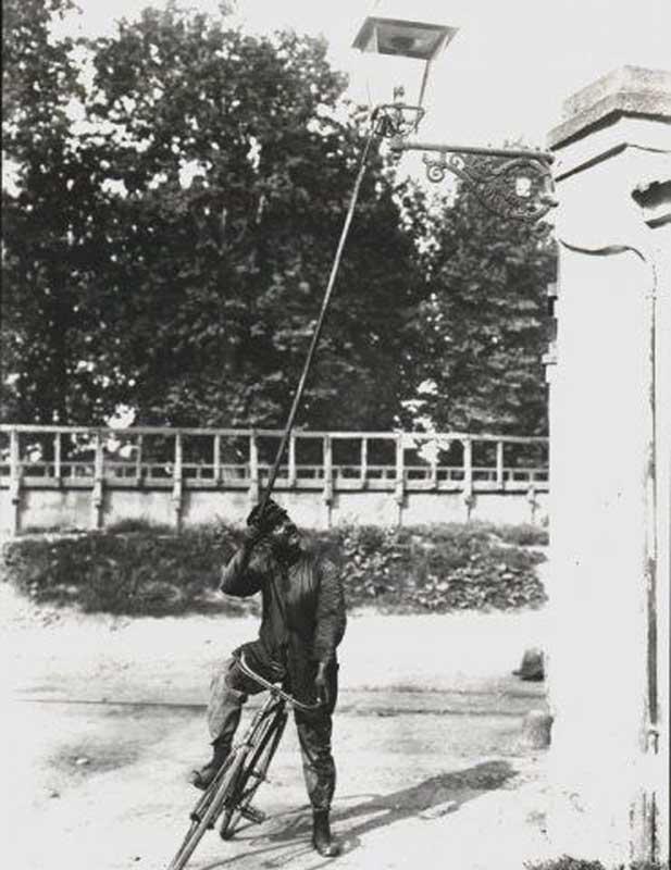 """Prima metà degli anni '10 circa: un """"Lampionee"""" (Lampionaio) in bicicletta a Milano ripreso mentre accende un lampione a gas."""