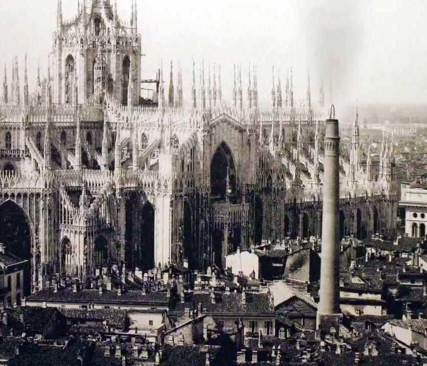 Fotografia che riprende la ciminiera fumante della centrale di Santa Radegonda; sullo sfondo l'imponente struttura del Duomo di Milano.