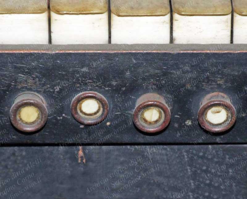 I quattro curiosi e minuscoli pistoncini a comando elettrico che sono posizionati sul frontalino delle tastiere del primo e del secondo manuale; erano stati previsti per l'inserzione di alcuni registri che di seguito elenco, iniziando da sinistra con il N°1. Prima tastiera: N°1-Annullatore / N°2-Principali / N°3-Tromba / N°4- Ripieno. Seconda tastiera: N°1-Annullatore / N°2-Viola da gamba / N°3-Oboe / N°4-Ripieno. Come si può notare non esistono numeri, targhette o riferimenti che indichino la funzione dei pulsanti, mentre per i numerosi pedaletti sottostanti non è così, in quanto sopra ognuno di essi, come ho anticipato, si trova scritto un numero a china. La curiosità di questa consolle consiste nell'avere le funzioni di ogni comando a pistoncino o a pedaletto specificate in due grandi cartelli manoscritti a china (vedi Fig.45), che fanno parte integrante della omonima consolle e che sono stati posizionati rispettivamente a sinistra e a destra, appena sopra i comandi a pomello di ogni registro (vedi Fig.37).